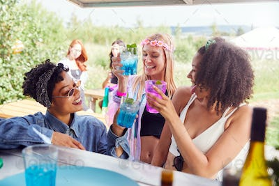 Female Friends Buying Drinks From Bar At Music Festival Making A Toast