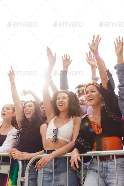Cheering Young Friends In Audience Behind Barrier At Outdoor Festival Enjoying Music
