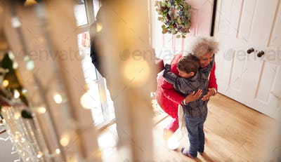 Excited Grandson Greeting Grandparents With Presents Visiting On Christmas Day