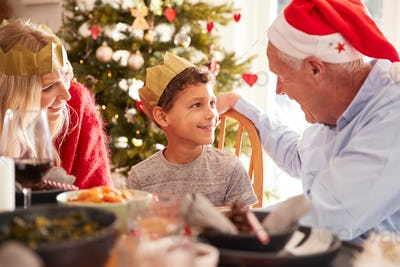 Mother With Son And Grandfather At Dining Table Enjoying Christmas Meal At Home Together
