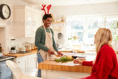 Couple Wearing Fancy Dress Antlers Drink Wine Whilst Preparing Dinner On Christmas Day