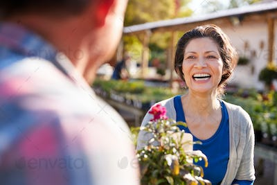 Mature Couple Outdoors Choosing Plants To Buy At Garden Center