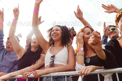 Young Friends In Audience Behind Barrier Dancing And Singing At Outdoor Festival Enjoying Music