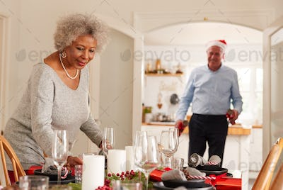 Senior Couple At Home Setting And Decorating Table For Meal On Christmas Day