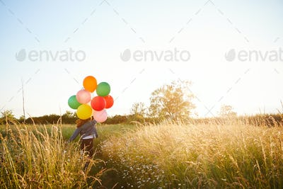 Rear View Of Two Female Friends Camping Running Through Field With Balloons Against Flaring Sun