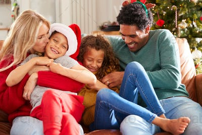 Parents Tickling Children As Family Sit On Sofa Celebrating Christmas Together
