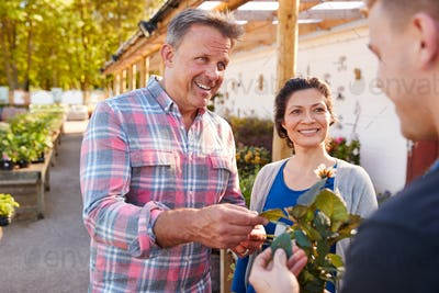Mature Couple Buying Plants From Male Sales Assistant In Garden Center