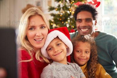 Portrait Of Family Posing For Selfie Sitting On Sofa Celebrating Christmas Together