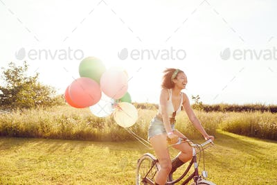 Young Woman Riding Bicycle Decorated With Balloons Through Countryside Against Flaring Sun