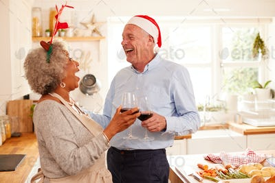 Senior Couple Wearing Fancy Dress Antlers Making A Toast Whilst Preparing Dinner On Christmas Day