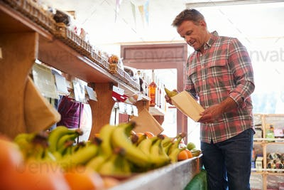 Male Customer With Paper Bag Buying Fresh Pears In Organic Farm Shop