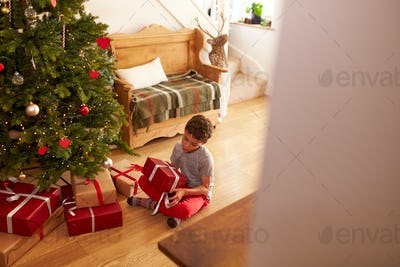 Excited Boy Opening Presents By Tree On Christmas Morning
