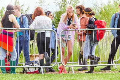 Group Of Young Friends Waiting Behind Barrier At Entrance To Music Festival Site