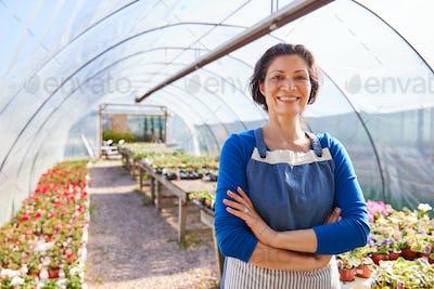 Portrait Of Mature Woman Working In Garden Center Greenhouse