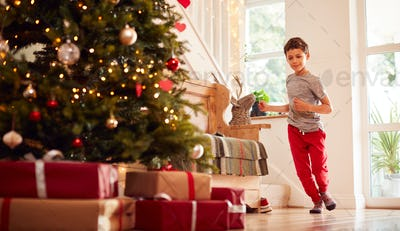 Excited Boy Running To Open Presents By Tree On Christmas Morning