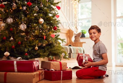 Portrait Of Excited Boy Opening Presents By Tree On Christmas Morning