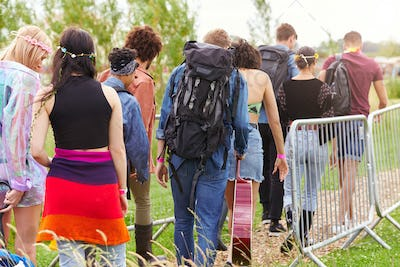 Rear View Of Friends At Entrance To Music Festival Walking Through Security Barriers