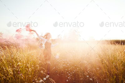Two Female Friends Camping At Music Festival Running Through Field With Smoke Flare