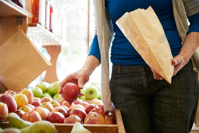 Close Up Of Woman Customer With Paper Bag Buying Fresh Apples In Organic Farm Shop