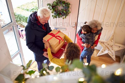 Excited Grandchildren Greeting Grandparents With Presents Visiting On Christmas Day