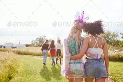 Rear View Of Female Friends Walking Back To Tent After Outdoor Music Festival