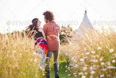 Young Romantic Couple Walking Through Field Towards Teepee On Summer Camping Vacation