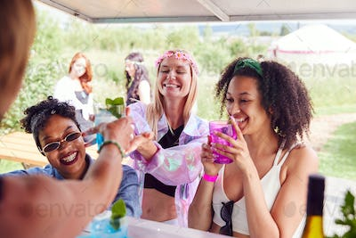 Female Friends Buying Drinks From Bar At Music Festival