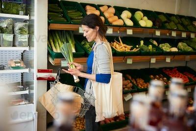 Female Customer With Shopping Basket Buying Fresh Leeks In Organic Farm Shop