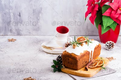 Fruit loaf cake dusted with icing, nuts and dry orange on stone background. Christmas and Winter