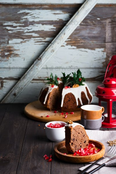 Christmas cliced chocolate cake with white icing and pomegranate kernels, cups and red lantern