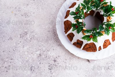 Christmas homebaked dark chocolate bundt cake decorated with white icing and holly berry branches on