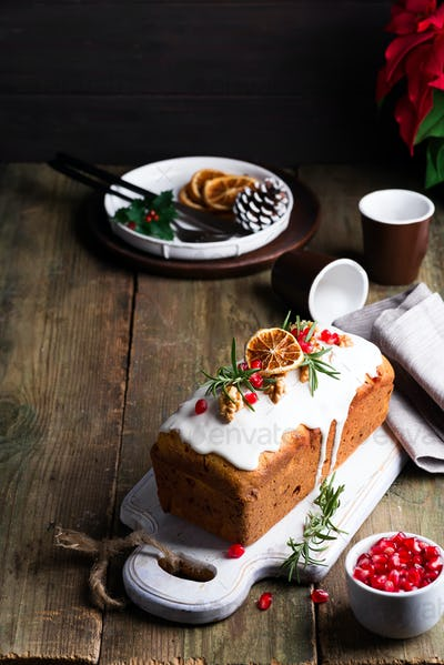 Fruit cake dusted with icing, nuts, kernels pomegranate and dry orange on old wooden background