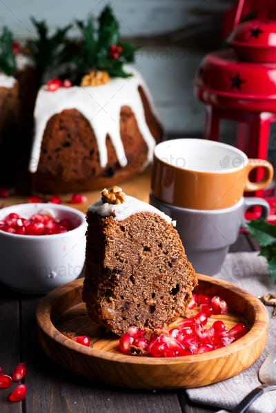 Christmas cliced chocolate cake with white icing and pomegranate kernels on a wooden dark background
