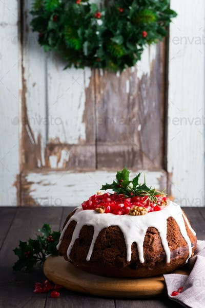 Christmas homebaked chocolate cake decorated with white icing and pomegranate kernels against the