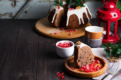 Christmas sliced chocolate cake with white icing and pomegranate kernels on a wooden dark background
