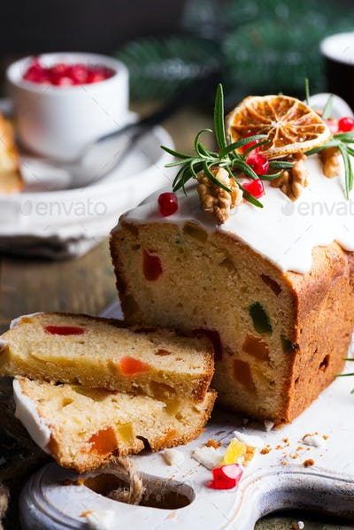 Fruit cake dusted sliced with icing, nuts, kernels pomegranate and dry orange close-up. Christmas