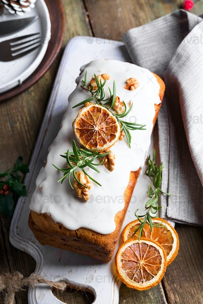 Fruit cake dusted with icing, nuts and dry orange on old wooden background. Christmas and Winter
