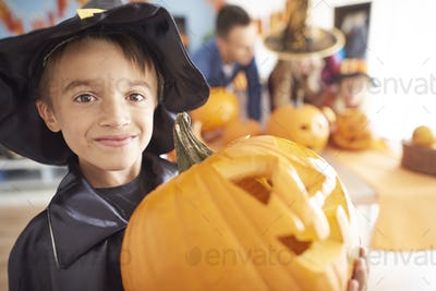 Little boy with big Halloween pumpkin