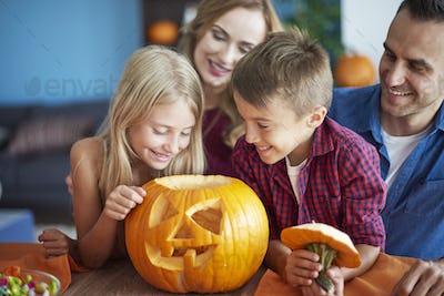 Family with scary Halloween pumpkin