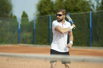 Man playing tennis on sunny day