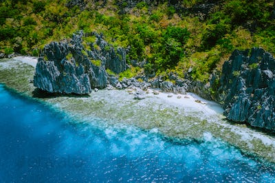 Aerial view of beautiful tropical limestone rocks, blue ocean and coral reef edge at El Nido
