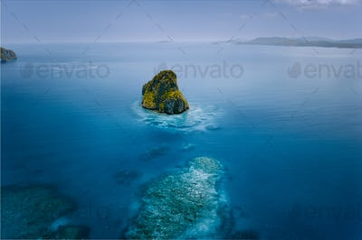 Aerial drone view of a beautiful secluded surreal cliff island surrounded by azure turquoise blue