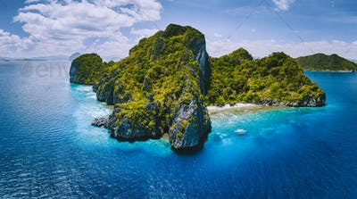 Aerial drone panorama view of tropical paradise island. Karst limestone rocky mountains surrounds by