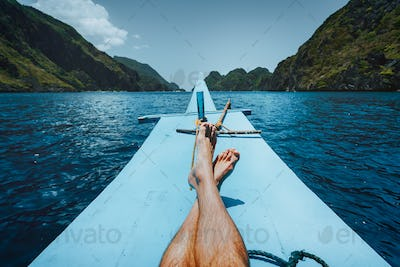 Legs of man on banca boat approaching tropical island. travel, relaxation and vacations concept