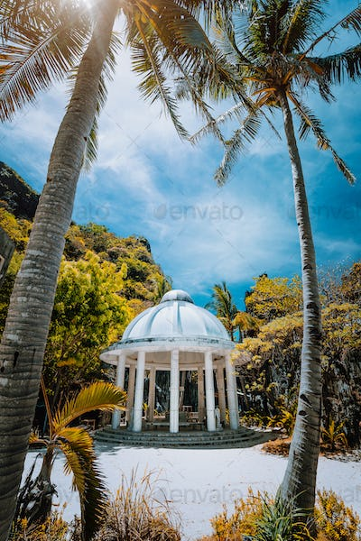 Abandoned Matinloc Shrine between two palm trees at the western coast of Matinloc Island at Palawan