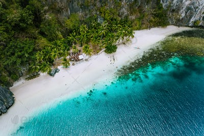 Aerial drone view of abandoned house hut on Pinagbuyutan Island in El Nido. Amazing white sand beach
