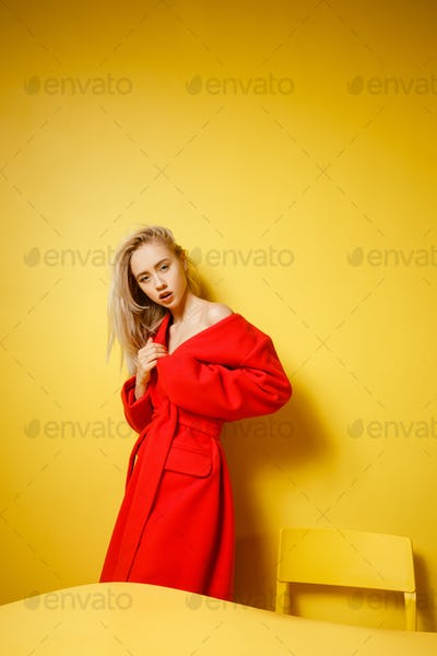 Fashion girl blogger dressed in stylish red coat is standing by the yellow table on the background