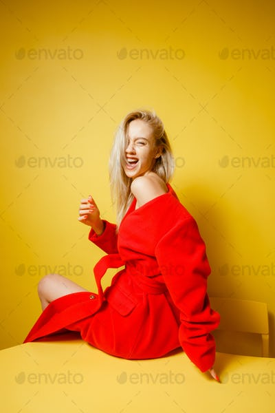 Laughing fashion girl blogger dressed in stylish red coat sitting on the yellow table on the
