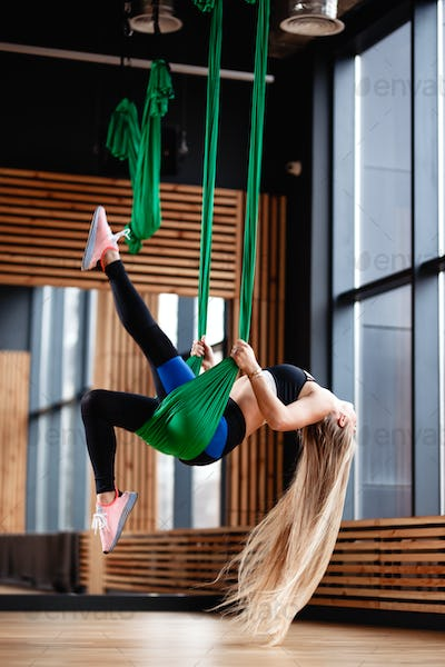 Slender young girl with long blond hair dressed in the sport clothes is doing fitness on the green