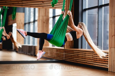 Athletic young girl with long blond hair dressed in the sport clothes is doing fitness on the green